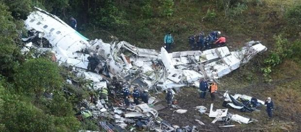 Na imagem os destroços do avião e a equipe de resgate trabalhando.