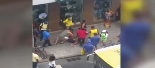 Na imagem um homem de camisa verde está sentado em cima das pernas do jovem imobilizando-o, enquanto outras pessoas assistem à cena.