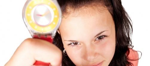 Immagine di repertorio, donna con un'orologio in mano.