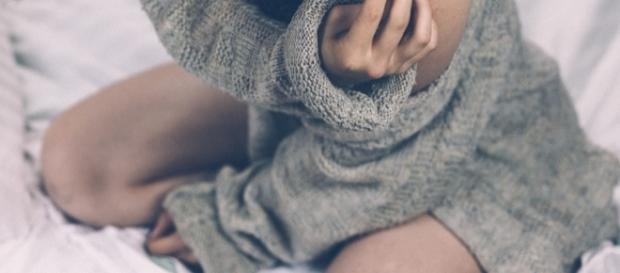 Mujer vistiendo jersey gris en la cama