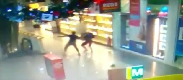 Na imagem o momento em que o freguês impede que o bandido armado assalte a loja do shopping.
