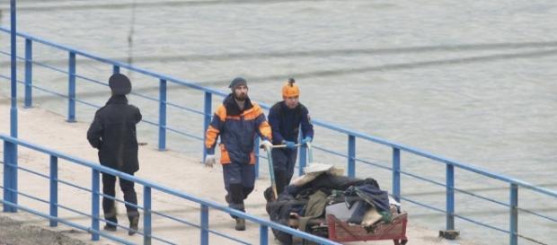 Equipe de Resgate Russa transportando restos da fuselagem do avião que caiu no Mar Negro. (Foto: REUTERS/Yevgeny Reutov )