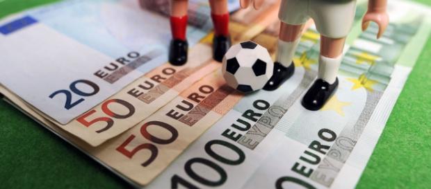 Pelota de fútbol de juguete encima de billetes