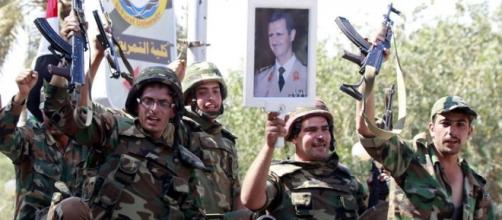Militari siriani espongono l'immagine di Assad
