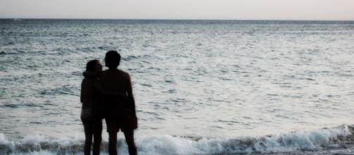 Una pareja abrazada contempla el mar.