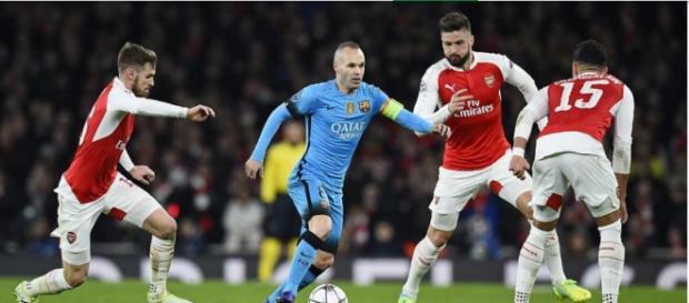 Iniesta manejando el balón rodeado de tres rivales
