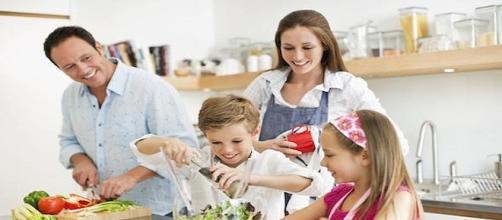 una familia en lo cocina haciendo la comida