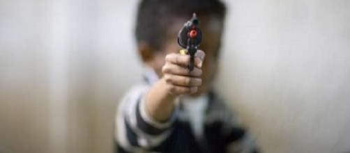 Menor de edad sosteniendo un arma