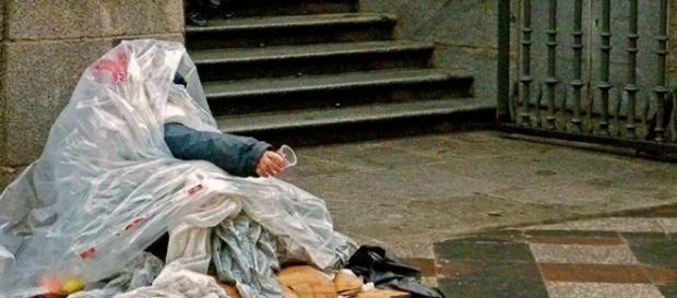 Un mendigo se guarece de la lluvia.