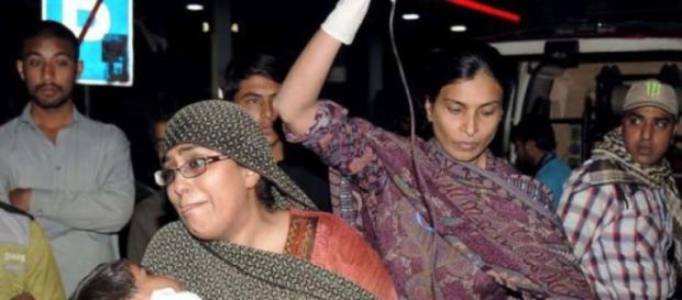 Una mujer intenta salvar a su hija herida en el atentado.
