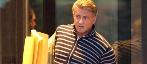 Stallone dirigiéndose al set con un guión.