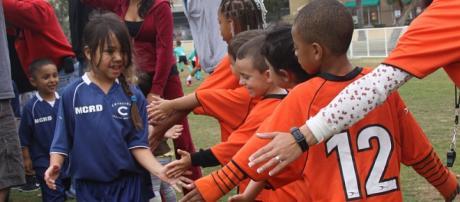 Crianças cumprimentando-se. (Wikipedia).