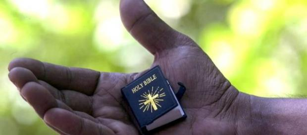 Una Bibbia in miniatura nella mano di un uomo
