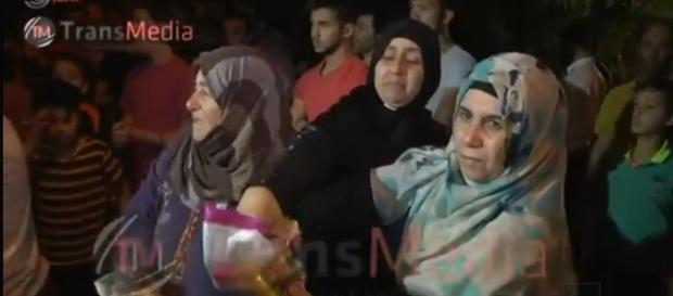 Abu Srour's relatives hand out candies to celebrate his Shaheed status. Screenshot from Israel television news broadcast.