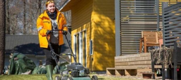 Trabajadora de correos finlandés cortando el cesped