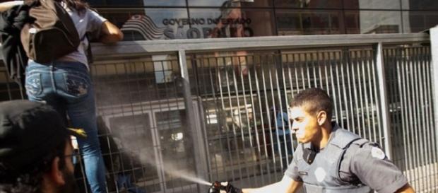 Policial usa spray para evitar a entrada dos estudantes