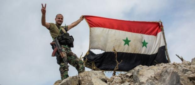 Soldado del ejército sirio mostrando bandera.