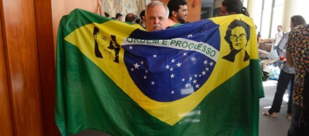 Foto: Tomaz Silva/Agência Brasil - Petista segura bandeira com foto de Lula e Dilma