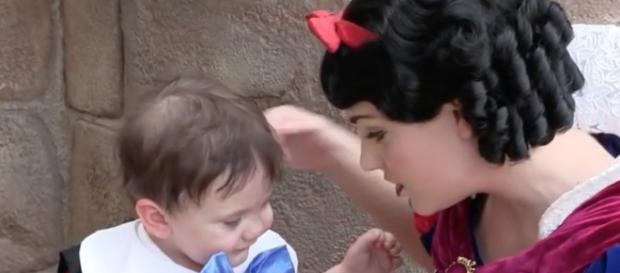 Il bambino e Biancaneve al parco divertimenti di Walt Disney