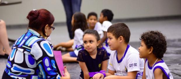 Estudantes interagindo com professora, em visita ao STF