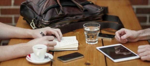Pareja de emprendedores en una reunión anotando ideas.