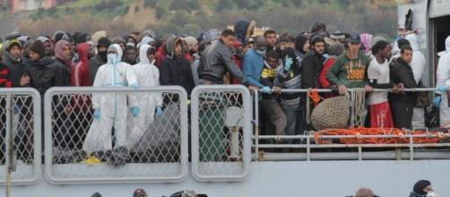 Operazioni di sbarco per un folto gruppo di migranti in un porto italiano