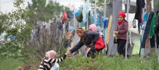 Una refugiada con un bebé en brazos es ayudada por otra refugiada