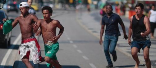 Homens (sem camisa) fogem após tentativa de assalto no Rio