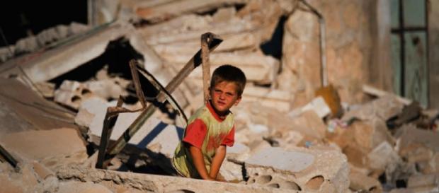 Niño entre los escombros de un edificio en Siria