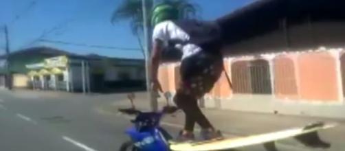 Motociclista surfa enquanto pilota sua moto.