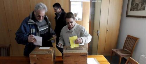 Dos ancianos suizos metiendo la papeleta en la urna