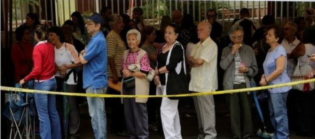 Ciudadanos haciendo cola para validar sus documentos y huellas