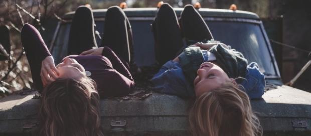 Chicas tumbadas hablando sobre un coche