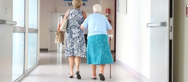 Una anciana acompañada por los pasillos de un hospital