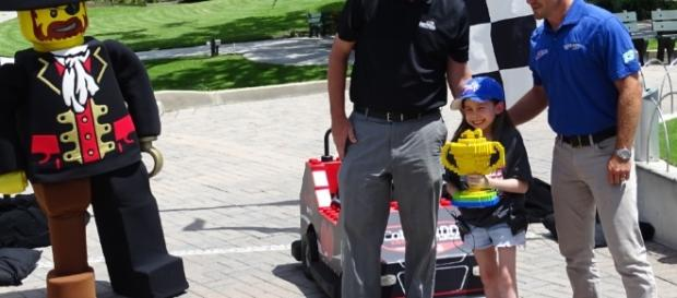 Make-A-Wish kid Layla Popoff gets a Lego trophy after beating NASCAR's Casey Mears/Photo by Barb Nefer