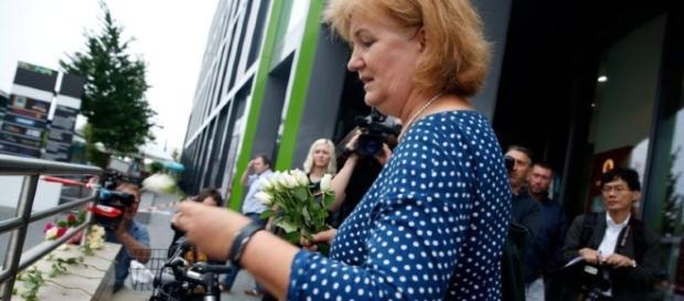 Personas poniendo flores y velas a las víctimas