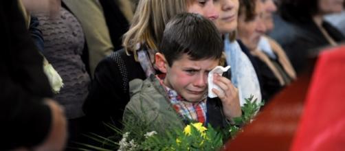 Irmão mais novo se despede de Segei durante o funeral