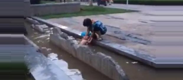 Na imagem a criança nua é forçada a ficar na água suja. Fotos da internet.