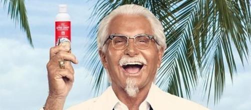 """Il """"Colonnello Sanders"""" (George Hamilton) mostra una bottiglietta di KFC Extra Crispy Sunscreen"""