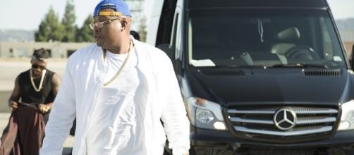 Rapper E-40 (Earl Stevens) walking to the charter plane