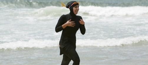 Une nageuse en burkini sur une plage