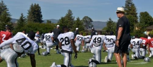 Coach Jack Del Rio watching over pre-camp stretching.