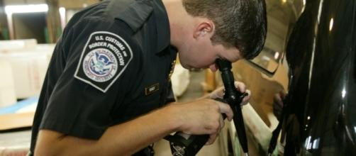 A CBP officer uses a high-tech device to peek inside a drum for contraband. - cbp.gov