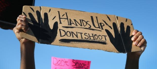 """BLM protester holding up """"hands up, don't shoot"""" sign. - google images"""