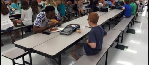 Campione di footbal siede vicino a ragazzo autistico
