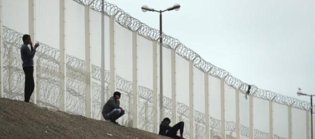 Migranti addossati alla barriere metalliche già esistenti. Foto BBC