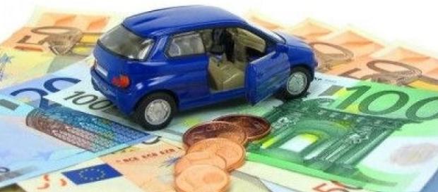 Un modellino di una macchina su una serie di banconote
