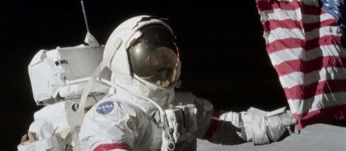 Eugene Cernan l'ultimo uomo sulla Luna tocca la bandiera americana nel 1972 nella regione lunare di Taurus Littrows