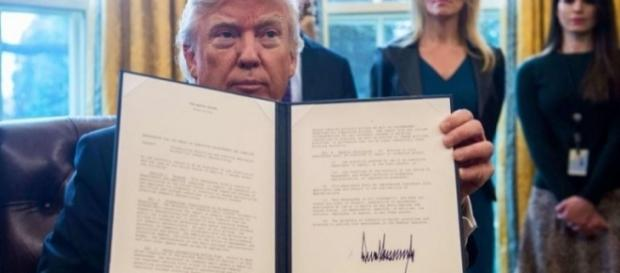 Donald Trump trzymający dekret o zakazie wstępu dla muzułmańskich migrantów (fot. thesun.co.uk)
