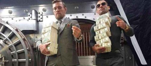 McGregor e seu companheiro de treinos posam com pilhas de dinheiro das lutas ganhas
